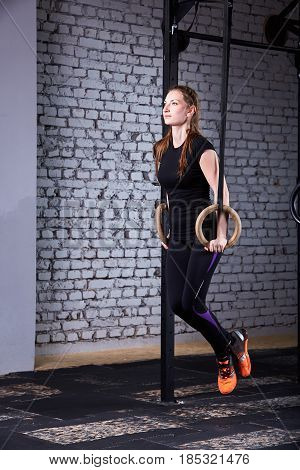 Young attractive woman doing cross fit push ups with rings against brick wall in the cross fit gym. Sporty woman in the black sportwear, t-shirt, leggings and sportive shoes. Healthy lifestyle.