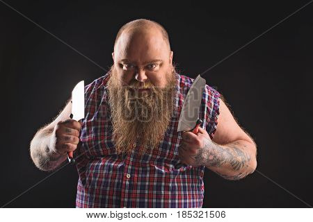 I will slaughter you. Angry thick man is holding machete. He is standing and looking at camera with irritation. Isolated on black background