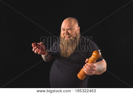 Portrait of hungry fat man holding raw meat and tool with spices. He is grinning to camera with anger. Isolated and copy space