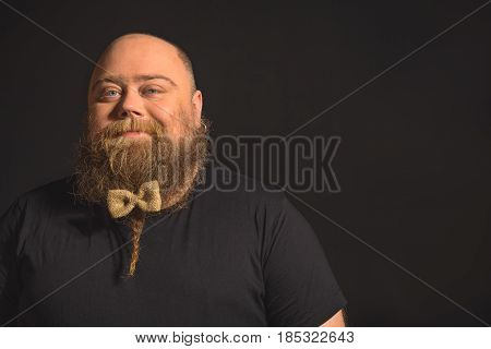 I am the real gentlemen. Portrait of joyful fat man standing with bow on his beard and smiling. Isolated and copy space in right side