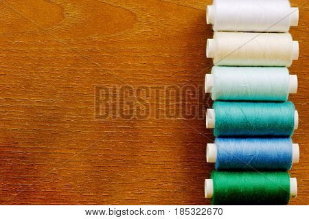 Vertical row of sewing thread spools of white blue and green colors. Sewing tools frame