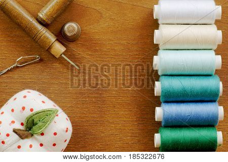 Sewing tools frame with a row of colorful thread spools and a vintage sewing set. Top view
