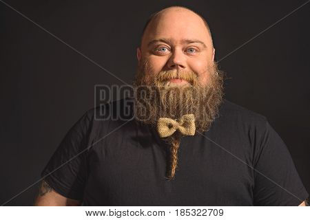 Waist up portrait of happy fat man with pretty bow on his beard. He is looking at camera with joy and smiling. Isolated