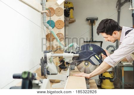 Young turner cuts board with circular saw. Mans hands holding protective equipment housing and wooden plank. Grinding wheels fixed on stand