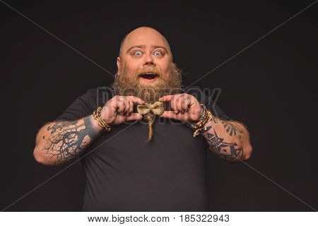 Portrait of happy fat man wearing small bow on his large beard. He is standing and laughing with excitement. Isolated