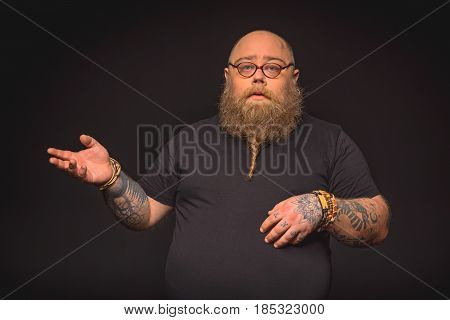Waist up portrait of smart fat man explaining something with seriousness. He is standing with eyeglasses and gesturing. Isolated on black background