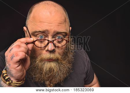 Portrait of serious thick guy looking at camera pensively. He is adjusting eyeglasses. Isolated and copy space in right side
