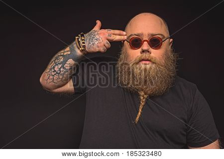 Portrait of depressed thick hipster touching two fingers to his temple like gun. He is wearing sunglasses and has stylish beard. Isolated