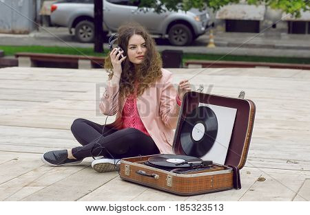 Music addicted girl having fun with headphones and a portable stereo vinyl record system.