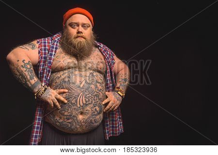 Do you want to tell me something. Bully male fatso is standing with arms akimbo and looking at camera seriously. Focus on his big bare belly. Isolated and copy space