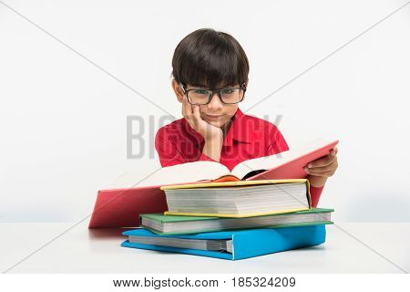 indian cute little boy or kid reading book over study table, isolated over white background