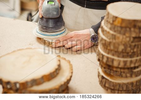 Male holding wooden round workpiece and processing with grinding machine using abrasive wheel as cutting tool. Human working in protective apron. Mopping up of wood circles.