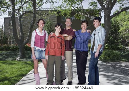 Caucasian family standing in driveway of home