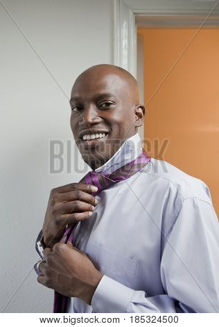 African American businessman tying tie