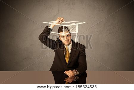 An elegant, successful university student drawing himself a square academic mortarboard cap with a chalk in front of grey wall background concept