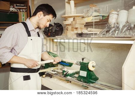 Young turner engages in wood carving on lathe for wood. Wooden blank clamped in metal centers of machine-tool. Worker in overalls holding hand milling cutters.
