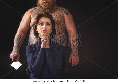 Do not eat me. Scared young girl is sitting and praying while joining her hands together. Fat man is standing beside her with machete. Isolated and copy space