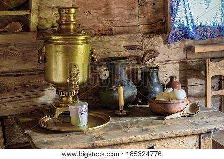 Samovar and pottery on the table in the old wooden house.