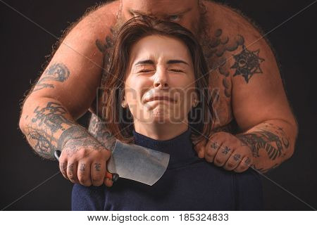 Hungry fat man is keeping big knife near female neck. Young woman closed eyes with fear. Portrait. Isolated
