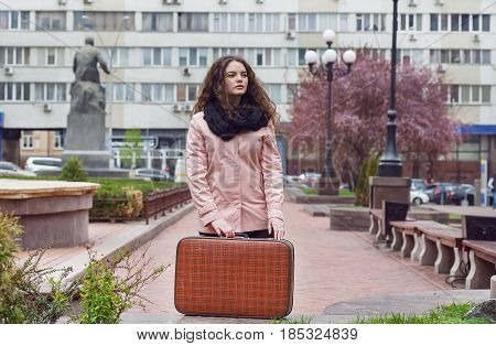 Alone girl staying on empty street with retro suitcase. Big city loneliness.