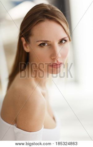 Portrait of beautiful girl in white blouse with bare shoulders