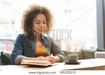 cheerful female writing in copybook while sitting at table in comfortable apartment. Copy space
