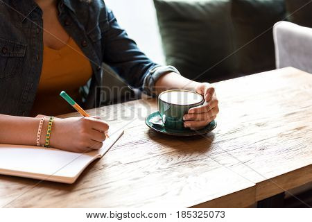 close up hand of woman keeping cup of coffee. She drinking it and making notes in scribbling-diary at desk in room