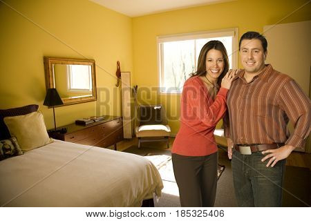 Husband and wife standing in bedroom