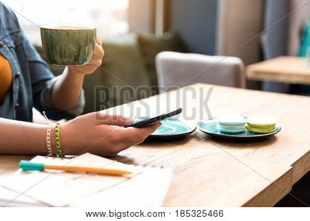 close up arm of girl writing message in mobile. She drinking cup of beverage while sitting at table