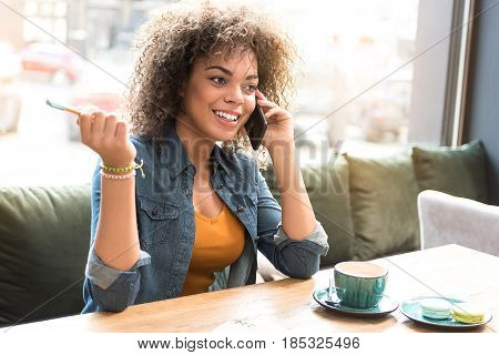 Portrait of mulatto female expressing happiness while telling at cellphone. She sitting at desk in cafe