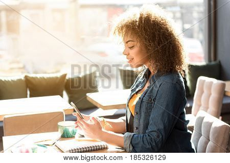 side view cheerful mulatto woman looking at mobile. She sitting at desk in cafe