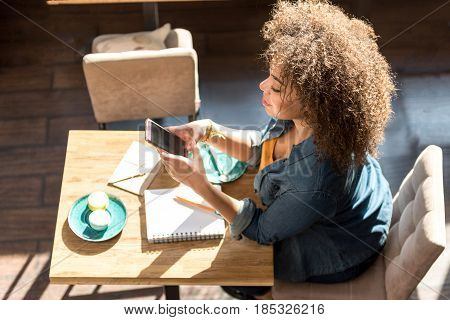 Top view of smiling mulatto female looking at mobile in cafe. She sitting at desk