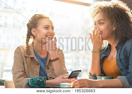 cheerful african woman chatting with beaming caucasian female while locating at table in confectionary shop