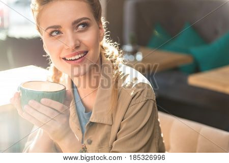 Portrait of female demonstrating dreaminess while tasting mug of hot beverage in cafe