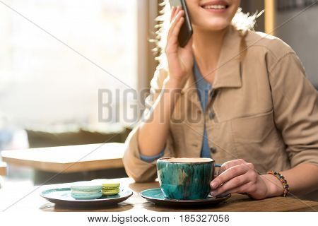 Cheerful young female talking at mobile. She tasting mug of beverage while sitting at table in cafe