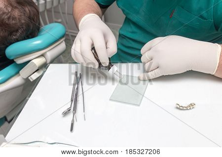 A dentist prepares an implant in the clinic .
