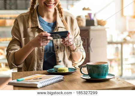 Cheerful girl taking photo of delicious cakes while sitting at desk in confectionary shop