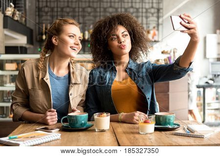 Happy mulatto woman making fun with beaming caucasian friend while doing image by mobile. Selfie concept