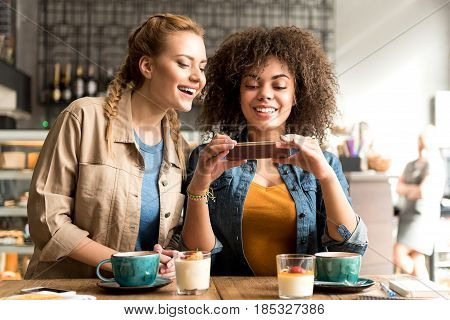 Cheerful female looking at cellphone of outgoing african girl in confectionary shop