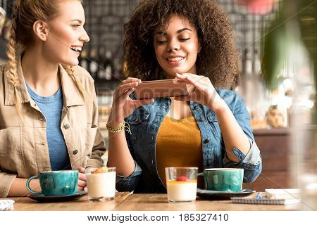 portrait of smiling woman telling with beaming mulatto female in cafe while using phone
