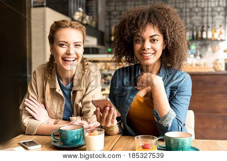 Portrait of outgoing caucasian friend telling with beaming mulatto girl in confectionary shop. They sitting at desk