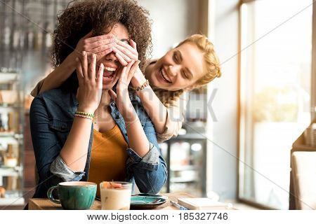 Happy girl closing eyes by hands her laughing friend while sitting at desk in confectionary shop