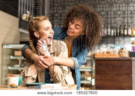Caucasian woman expressing surprise while beaming african friend embracing her. She sitting at desk in confectionary shop