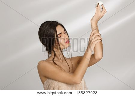 Woman in bath towel  applying moisturizer on left hand after bathing. Sking and beauty care.