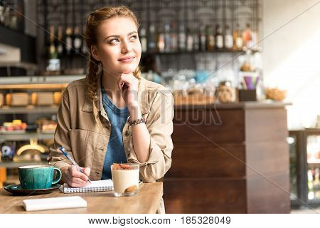 Smiling woman expressing thoughtfulness while making notes in scribbling-diary in confectionary shop