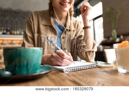 Low angle focus on female pen writing in copybook in cafe. Woman drinking cup of coffee