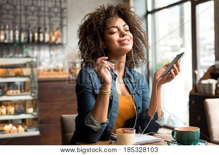 Portrait of mulatto woman expressing pleasure while listening music. She sitting at table in confectionary shop
