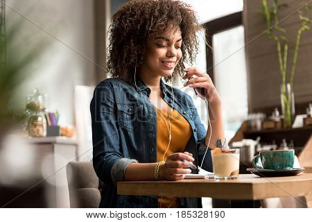 Low angle portrait of smiling female listening music while situating at desk in confectionary shop. She writing in copybook