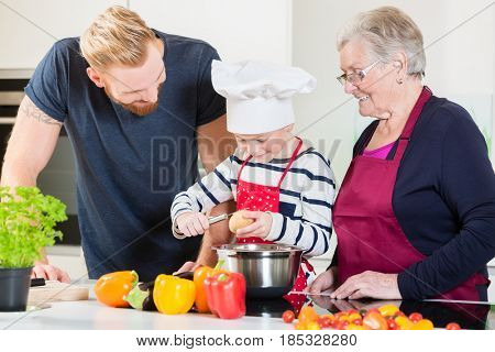 Mom, dad, granny and grandson together in kitchen preparing food