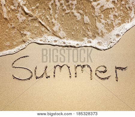 Summer written in the golden sand by the sea waves